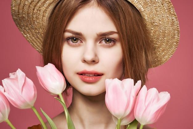 Femme avec bouquet de fleurs attrayant look glamour cadeau fond rose