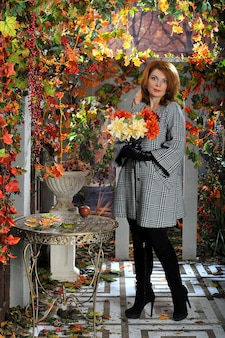 Femme avec un bouquet de fleurs dans la forêt d'automne