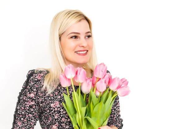 Femme avec bouquet de fleurs de printemps. femme modèle surprise heureuse sentant les fleurs. fête des mères. printemps