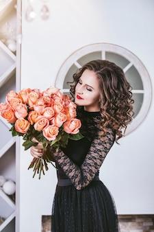 Femme avec bouquet de fleurs roses