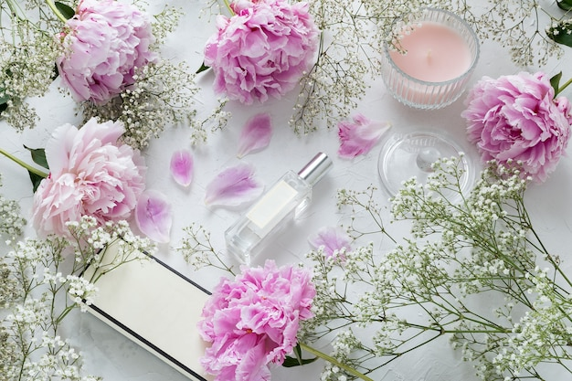 Femme, bouteille de parfum plat blogueur beauté poser, pivoines, fleurs de gypsophile sur marbre