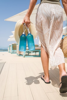 Femme avec des bouteilles d'eau au bord de la piscine