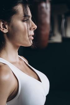 Femme de boxe posant avec sac de boxe. concept de femme forte et indépendante