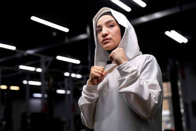 Femme de boxeur arabe en posture de combattant, frappant, engagée dans le sport, la boxe. au gym, au centre de fitness