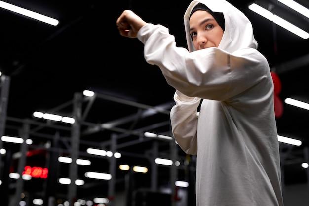 Femme de boxeur musulman confiant en posture de combattant, frappant, engagée dans le sport, la boxe. au gym, au centre de fitness
