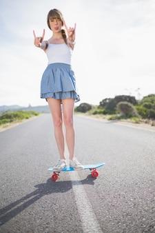 Femme branchée faisant des gestes de rock and roll tout en équilibre sur sa planche à roulettes