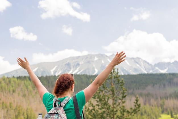 Femme, bras ouverts, sur, sommet montagne