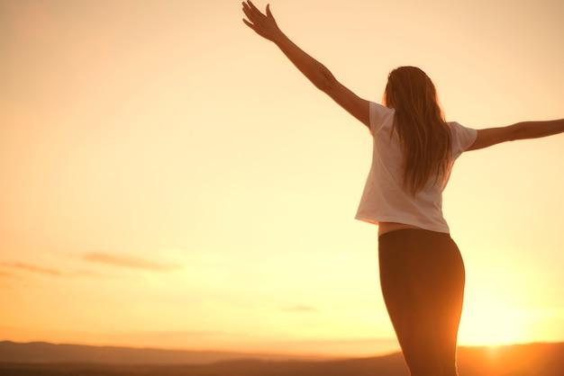 Femme les bras ouverts sous le coucher de soleil. concept de vie saine.