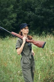 Femme sur les bras en plein air dans les mains d'une combinaison verte lifestyle air frais cap noir arbres verts sur