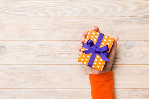 Femme bras tenant une boîte cadeau avec ruban de couleur sur une table en bois rustique jaune, vue de dessus
