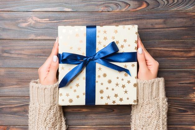 Femme bras tenant une boîte cadeau avec ruban de couleur sur une table en bois sombre, espace de copie vue de dessus