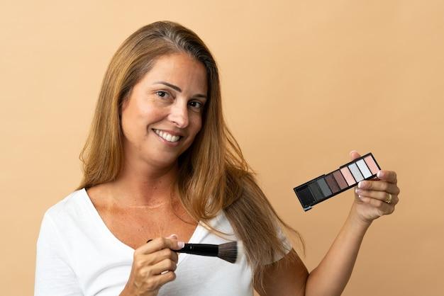 Femme brésilienne d'âge moyen isolée avec palette de maquillage