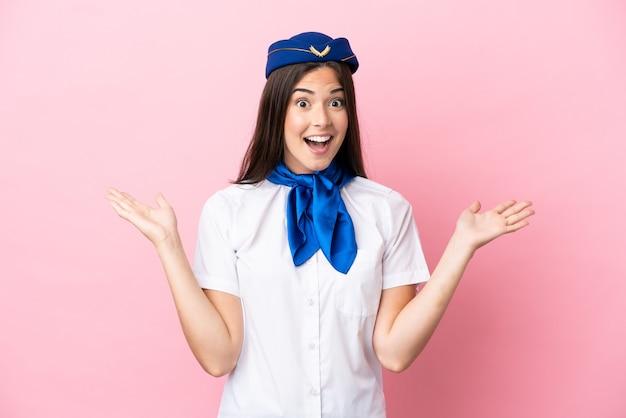 Femme brésilienne d'hôtesse d'avion isolée sur fond rose avec une expression faciale choquée