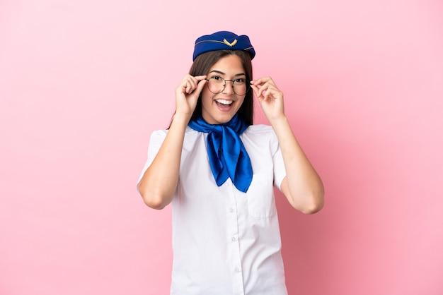 Femme brésilienne d'hôtesse d'avion isolée sur fond rose avec des lunettes et surprise