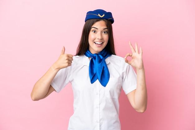 Femme brésilienne d'hôtesse d'avion isolée sur fond rose montrant le signe ok et le geste du pouce vers le haut