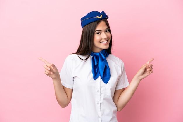 Femme brésilienne d'hôtesse d'avion isolée sur fond rose, pointant le doigt vers les latéraux et heureux
