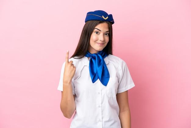 Femme brésilienne d'hôtesse d'avion isolée sur fond rose pointant avec l'index une excellente idée