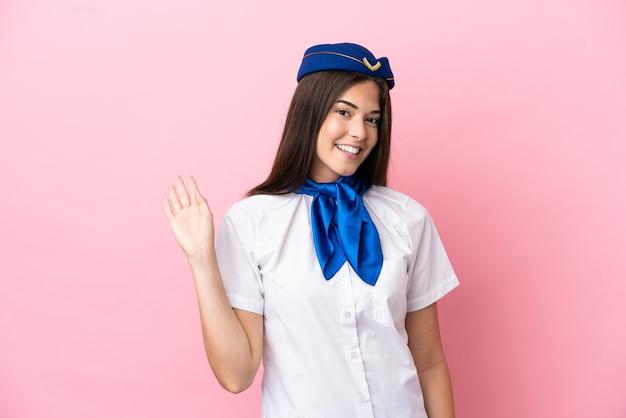 Femme brésilienne d'hôtesse d'avion isolée sur fond rose saluant avec la main avec une expression heureuse