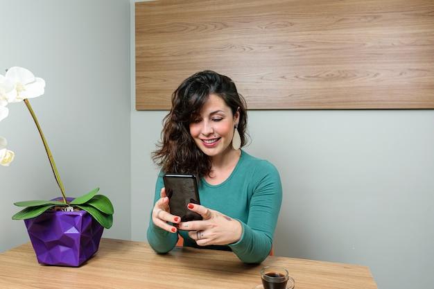 Femme brésilienne souriante, assise et interagissant avec son smartphone.