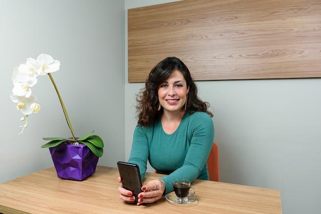 Femme brésilienne, souriante avec un smartphone dans les mains, à côté d'une tasse de café.