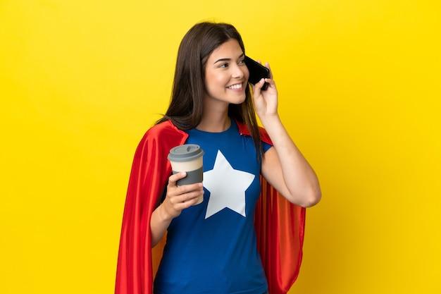 Femme brésilienne de super héros isolée sur fond jaune tenant du café à emporter et un mobile