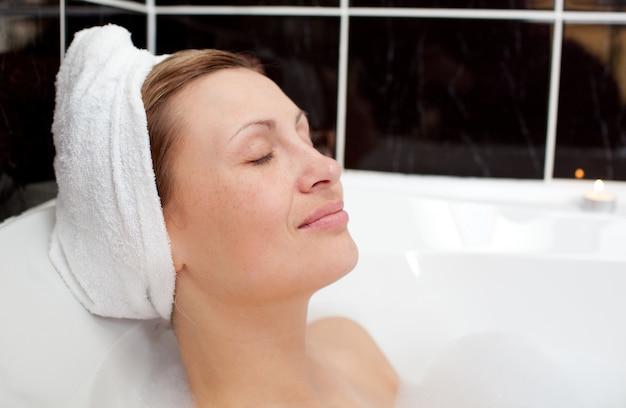 Femme brillante relaxante dans un bain moussant