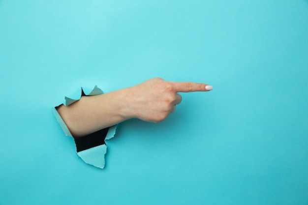 Femme brise le bras à travers le mur de papier bleu indique à droite à l'espace vide donne des conseils