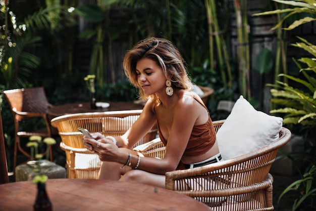 Femme bronzée aux cheveux courts en haut marron et short en jean bavardant au téléphone