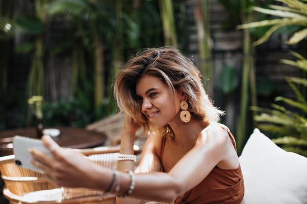 Une femme bronzée blonde dans des boucles d'oreilles faites à la main fait selfie et sourit