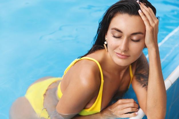 Femme bronzée détendue en bikini, yeux fermés, profitant de la piscine.