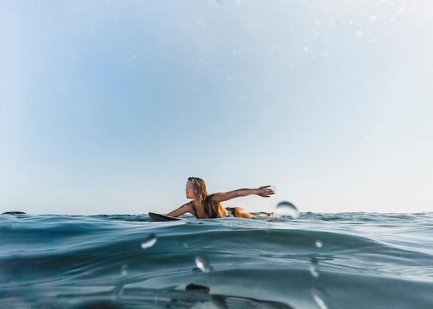 Femme bronzée nageant sur une planche de surf dans l'eau