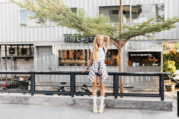 Femme bronzée souriante aux cheveux blonds posant sur fond de rue.