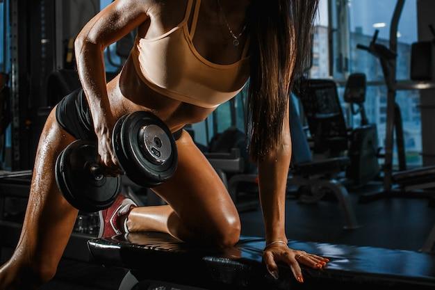 Femme bronzée sportive avec une forme parfaite, soulevant des haltères dans la salle de gym. fermer