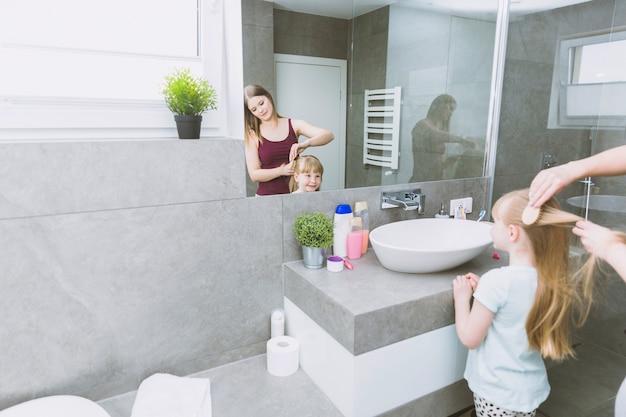 Femme brossage fille près de miroir