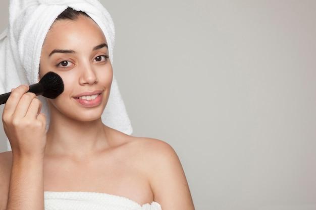 Femme à la brosse et au maquillage du visage
