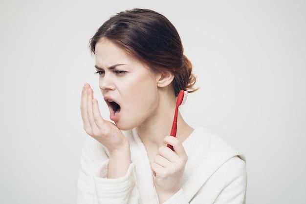 Femme avec une brosse à dents dans une salle blanche peignoir de procédures du matin.