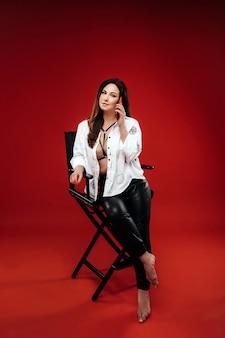 Femme brûlante sexy dans une chemise blanche assise sur une chaise avec un téléphone rouge sur fond rouge