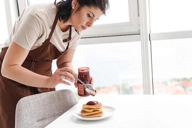 Femme brune adulte portant un tablier de cuisine dans la cuisine à la maison, et faire le petit déjeuner avec des crêpes et de la confiture