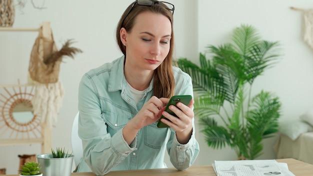 Femme brune à l'aide de smartphone alors qu'il était assis au bureau