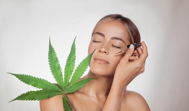 Femme brune appliquant l'huile liquide cbd pour les soins de la peau. portrait de jeune femme à la peau fraîche qui pose en studio. isolé sur fond gris