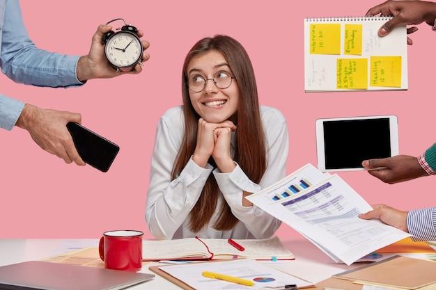 Femme brune assise au bureau entouré de gadgets et de papiers