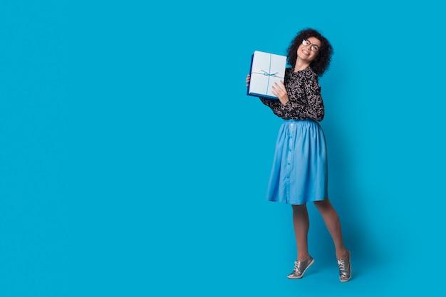 Femme brune aux cheveux bouclés annonce une boîte cadeau pour les vacances à venir sur un mur bleu avec un espace libre portant une robe