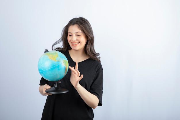 Femme brune aux cheveux longs choisit un endroit pour voyager sur le globe.