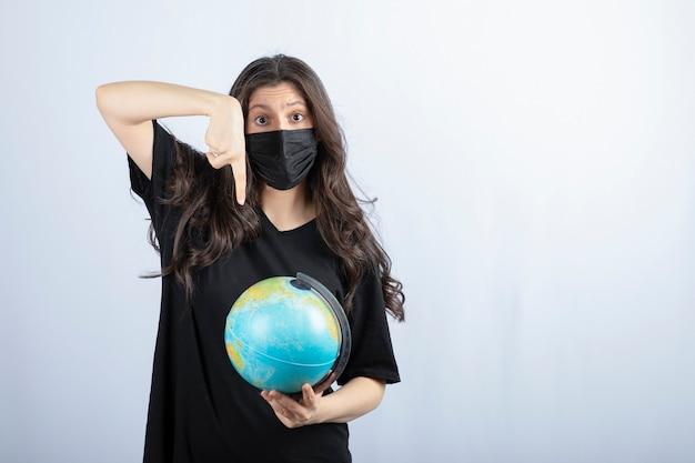 Femme brune aux cheveux longs dans un masque médical pointant sur le globe terrestre