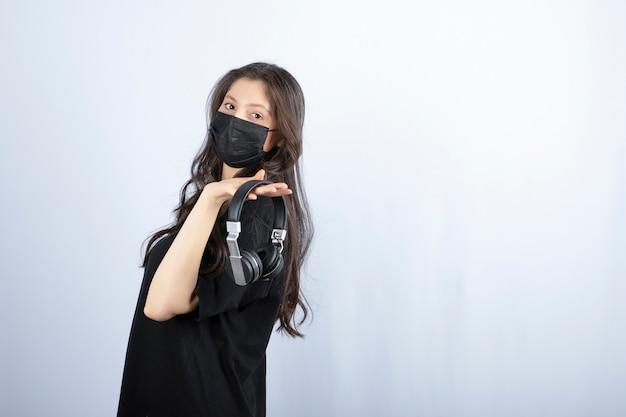 Femme brune aux cheveux longs dans un masque médical tenant des écouteurs.