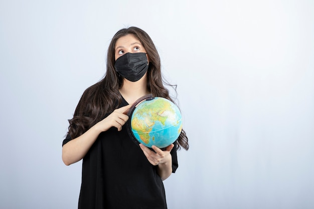 Femme brune aux cheveux longs en masque médical tenant le globe terrestre