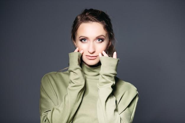 Femme brune aux grands yeux bleus touchant le visage par les doigts.