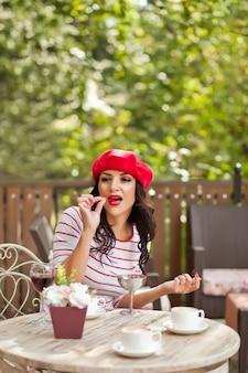 Femme brune aux lèvres rouges dans un bonnet rouge assis dans un café en plein air et manger des glaces.
