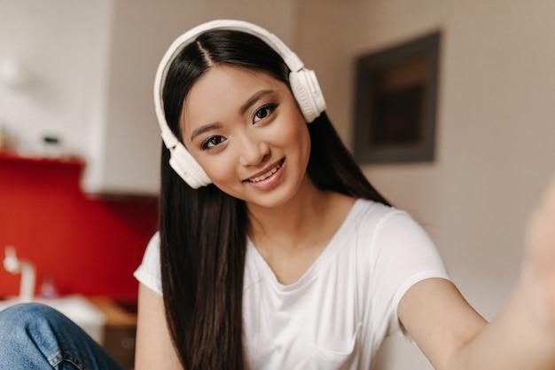 Femme brune aux yeux bruns dans des écouteurs massifs fait selfie et sourires mignons