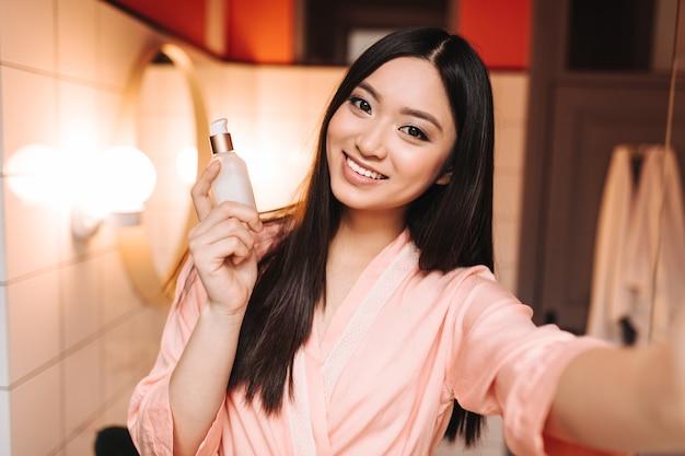 Une femme brune aux yeux bruns en robe de soie sourit doucement et prend un selfie avec un sérum pour le visage